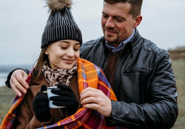 Vista frontal de um casal sorridente ao ar livre com um cobertor