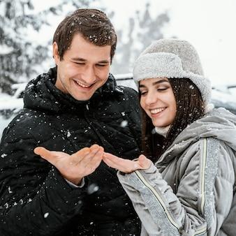 Vista frontal de um casal sorridente curtindo a queda de neve durante uma viagem