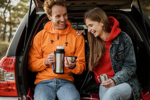 Vista frontal de um casal sorridente desfrutando de uma bebida quente no porta-malas do carro