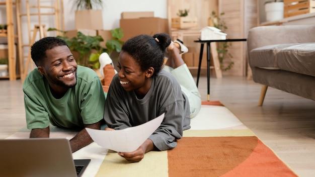 Vista frontal de um casal sorridente fazendo planos para redecorar a casa com um laptop