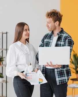 Vista frontal de um casal sorridente planejando juntos redecorar a casa