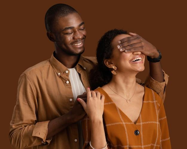 Vista frontal de um casal sorridente posando junto e se divertindo