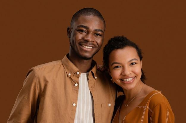 Vista frontal de um casal sorridente posando junto