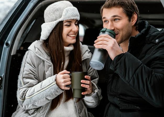 Vista frontal de um casal sorridente tomando uma bebida quente no porta-malas do carro durante uma viagem