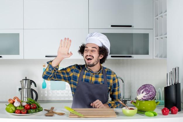 Vista frontal de um chef engraçado e emocional com legumes frescos, cozinhando com utensílios de cozinha e dizendo olá na cozinha branca