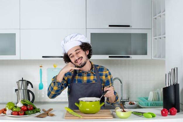 Vista frontal de um chef sorridente com legumes frescos e a mistura da refeição, fazendo um gesto de me ligar na cozinha branca