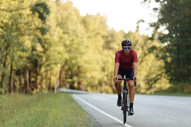 Vista frontal de um ciclista profissional vestido com roupas esportivas, correndo de bicicleta ao ar livre