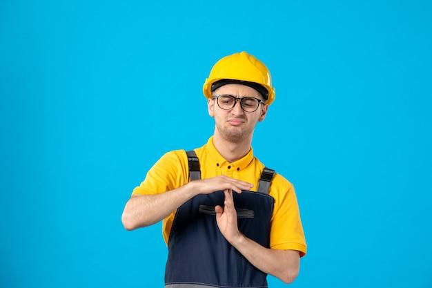 Vista frontal de um construtor masculino descontente, de uniforme, mostrando o sinal t na parede azul