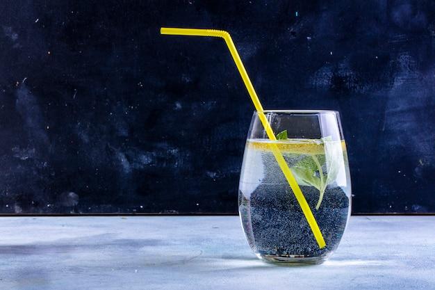 Vista frontal de um copo de água com uma fatia de limão com um canudo amarelo