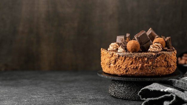 Vista frontal de um delicioso bolo de chocolate em estande com espaço de cópia