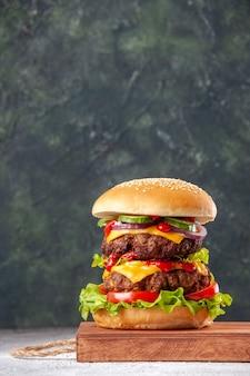 Vista frontal de um delicioso sanduíche caseiro na placa de madeira na superfície desfocada