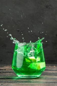 Vista frontal de um delicioso suco natural fresco em um copo com fundo preto