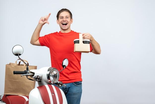 Vista frontal de um entregador de uniforme vermelho, sorridente, confiante e feliz, em pé perto de uma scooter, mostrando a ordem no fundo branco