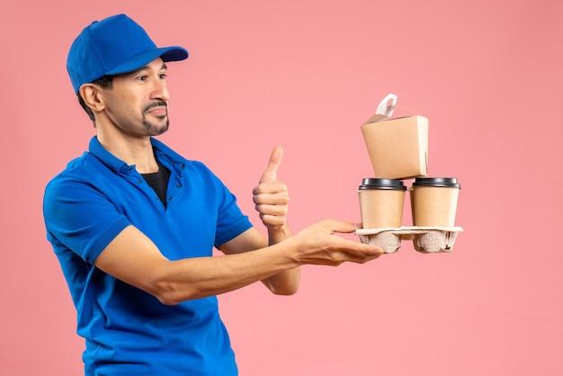 Vista frontal de um entregador louco e emocional usando um chapéu, segurando pedidos e fazendo gestos de ok