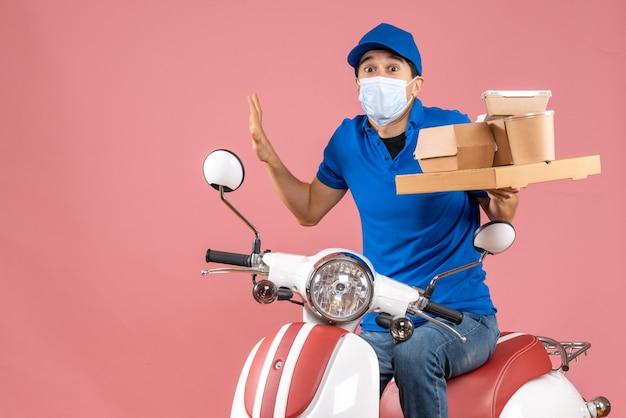 Vista frontal de um entregador perplexo, mascarado, usando um chapéu, sentado na scooter, entregando pedidos em fundo de pêssego