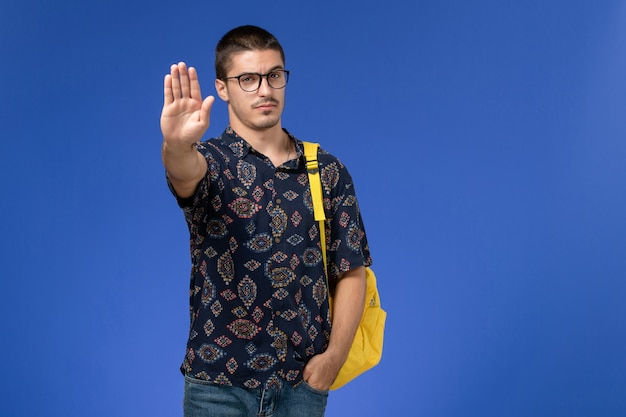 Vista frontal de um estudante do sexo masculino com camisa de algodão escura e mochila amarela mostrando o sinal de pare na parede azul