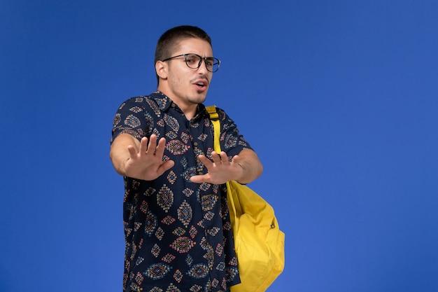 Vista frontal de um estudante do sexo masculino com camisa de algodão escura, mochila amarela e óculos de sol ópticos, posando na parede azul