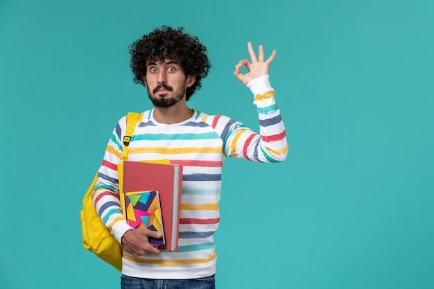 Vista frontal de um estudante do sexo masculino com camisa listrada colorida, usando uma mochila amarela, segurando arquivos e cadernos na parede azul