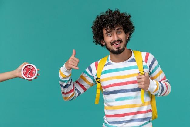 Vista frontal de um estudante do sexo masculino com camisa listrada e mochila amarela, posando com um sorriso na parede azul clara