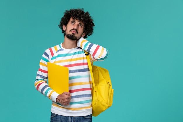 Vista frontal de um estudante do sexo masculino com camisa listrada e mochila amarela segurando arquivos com dor de pescoço na parede azul