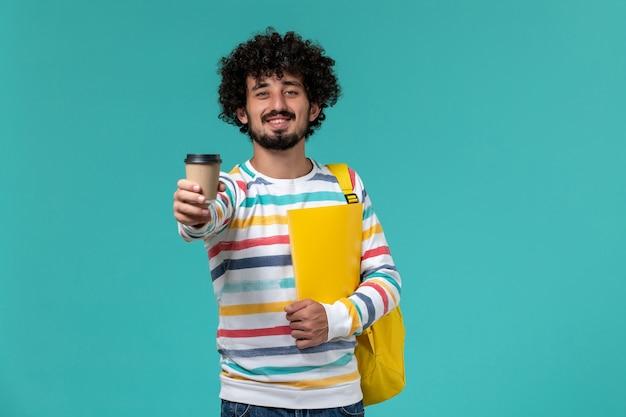 Vista frontal de um estudante do sexo masculino com camisa listrada e mochila amarela segurando arquivos e café na parede azul