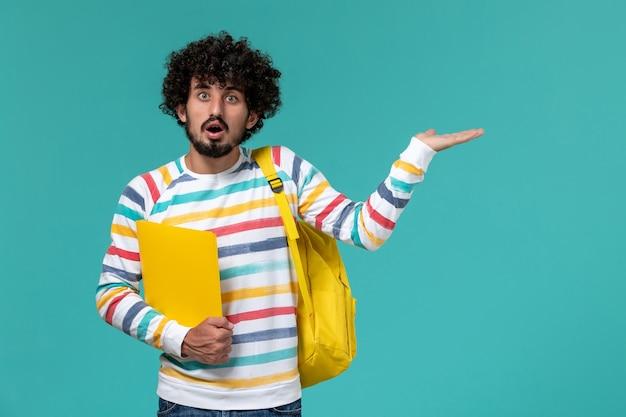 Vista frontal de um estudante do sexo masculino com camisa listrada e mochila amarela segurando arquivos na parede azul