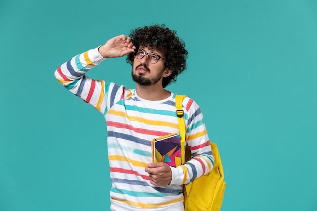 Vista frontal de um estudante do sexo masculino com camisa listrada e mochila amarela segurando cadernos na parede azul