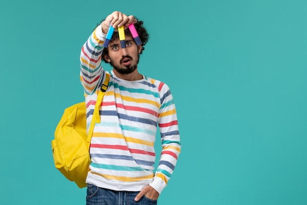 Vista frontal de um estudante do sexo masculino com camisa listrada e mochila amarela segurando canetas hidrográficas coloridas na parede azul