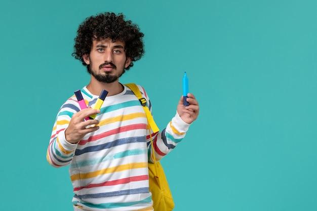Vista frontal de um estudante do sexo masculino com camisa listrada e mochila amarela segurando canetas hidrográficas na parede azul