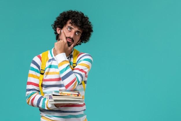 Vista frontal de um estudante do sexo masculino com camisa listrada e mochila amarela segurando livros e pensando na parede azul