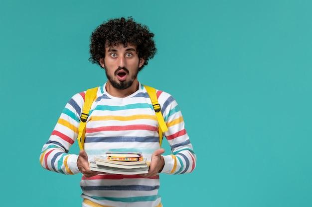 Vista frontal de um estudante do sexo masculino com camisa listrada e mochila amarela segurando livros na parede azul