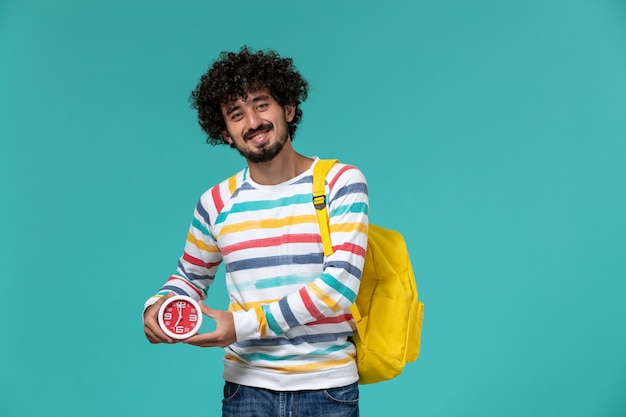 Vista frontal de um estudante do sexo masculino com camisa listrada e mochila amarela segurando relógios na parede azul