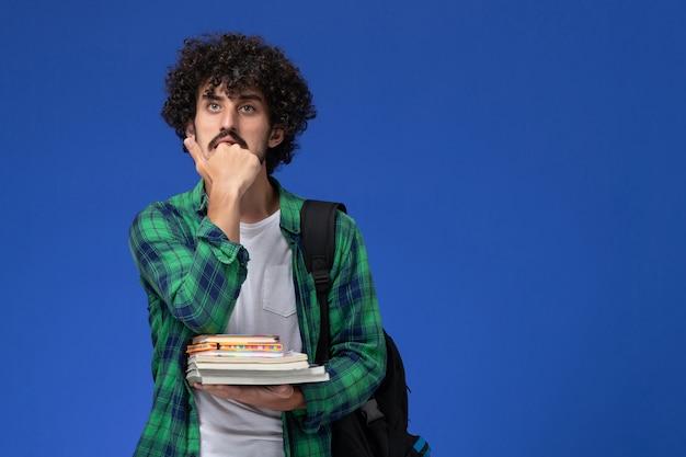 Vista frontal de um estudante do sexo masculino com camisa quadriculada verde com mochila preta segurando cadernos e arquivos na parede azul claro
