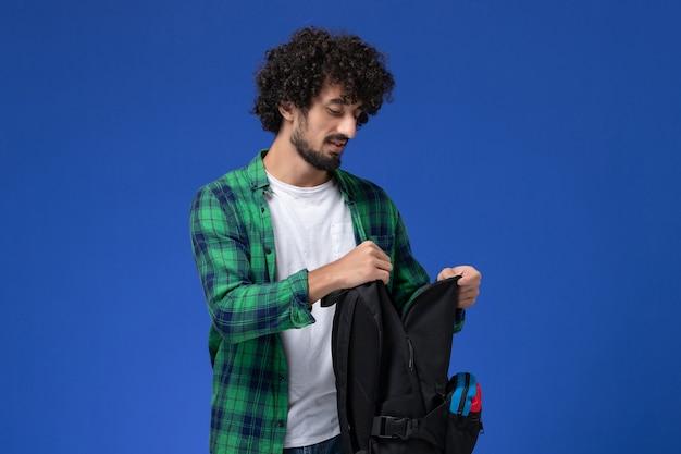 Vista frontal de um estudante do sexo masculino com camisa quadriculada verde segurando uma mochila preta na parede azul clara