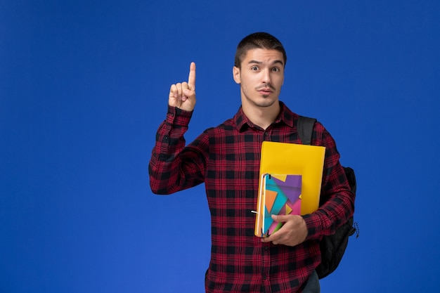 Vista frontal de um estudante do sexo masculino com camisa quadriculada vermelha com mochila segurando arquivos e cadernos levantando o dedo na parede azul