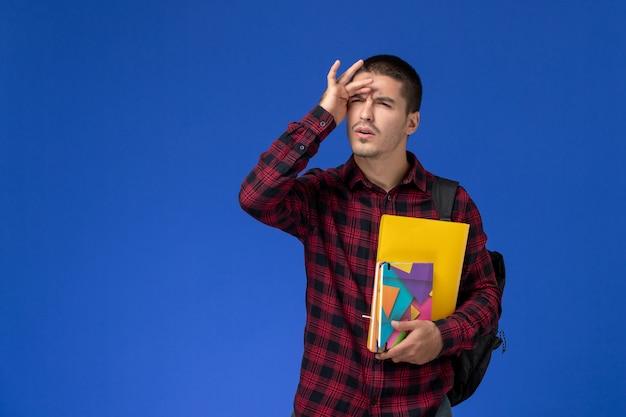 Vista frontal de um estudante do sexo masculino com camisa quadriculada vermelha com mochila segurando arquivos e cadernos na parede azul-clara