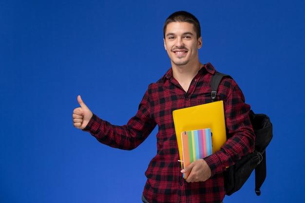 Vista frontal de um estudante do sexo masculino com camisa quadriculada vermelha com mochila segurando arquivos e cadernos na parede azul
