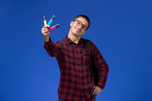 Vista frontal de um estudante do sexo masculino com camisa quadriculada vermelha com mochila segurando canetas de feltro coloridas na parede azul-clara