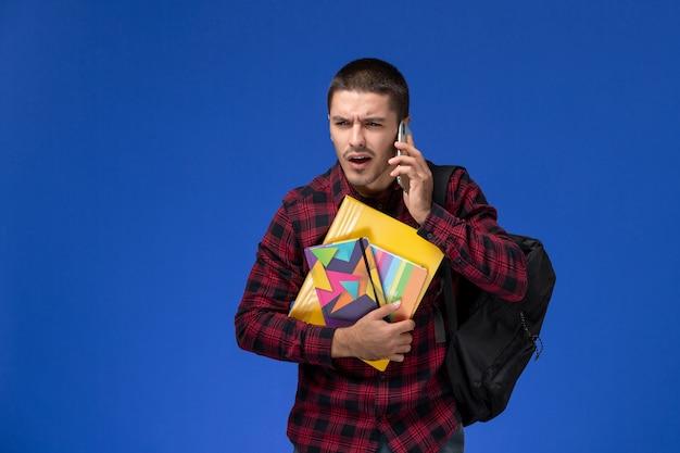 Vista frontal de um estudante do sexo masculino com camisa quadriculada vermelha com mochila segurando o caderno e arquivos falando ao telefone na parede azul