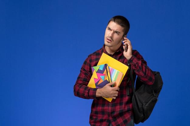 Vista frontal de um estudante do sexo masculino com camisa quadriculada vermelha com mochila segurando o caderno e arquivos falando ao telefone