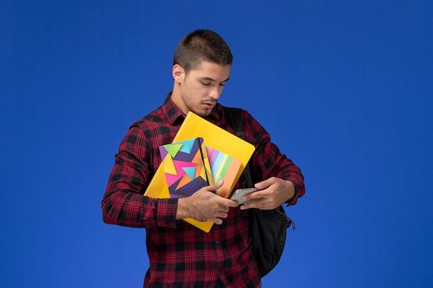 Vista frontal de um estudante do sexo masculino com camisa quadriculada vermelha com mochila segurando o caderno e arquivos usando seu telefone na parede azul