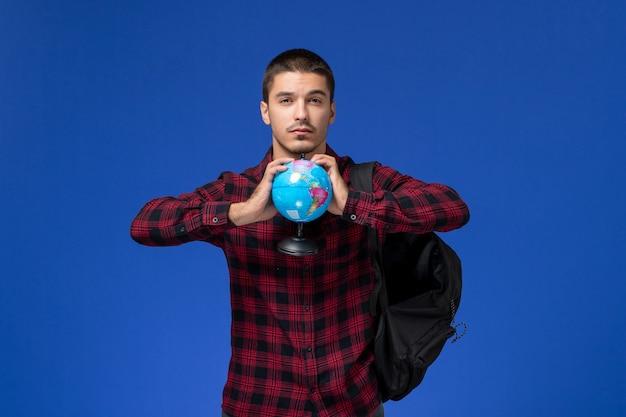 Vista frontal de um estudante do sexo masculino com camisa quadriculada vermelha com mochila segurando o globo redondo na parede azul-clara