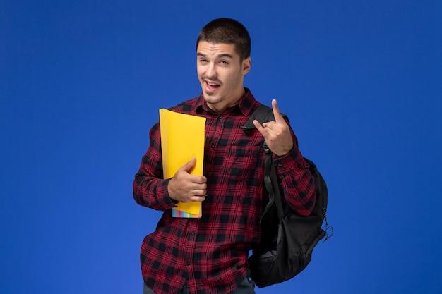 Vista frontal de um estudante do sexo masculino com camisa quadriculada vermelha com mochila segurando pastas amarelas na parede azul