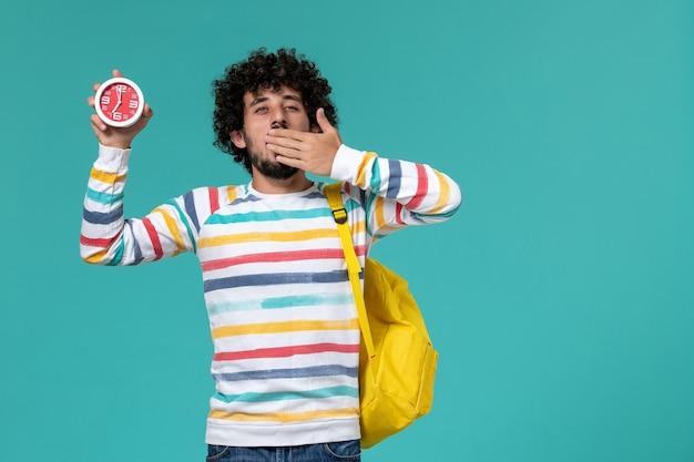 Vista frontal de um estudante do sexo masculino com mochila amarela segurando relógios bocejando na parede azul-clara