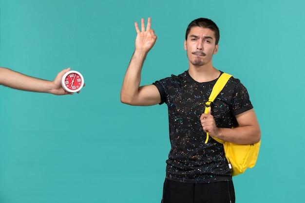 Vista frontal de um estudante do sexo masculino em uma mochila de camiseta amarela escura posando na parede azul claro