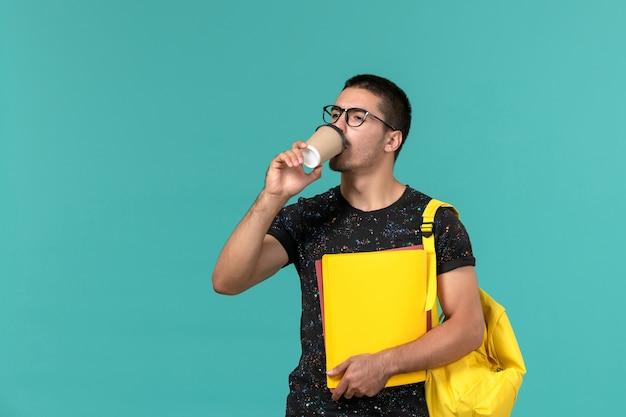 Vista frontal de um estudante do sexo masculino em uma mochila de camiseta amarela escura segurando arquivos diferentes e bebendo café na parede azul