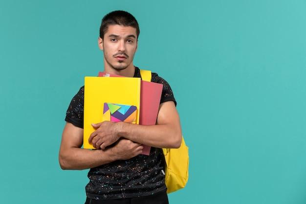 Vista frontal de um estudante do sexo masculino em uma mochila de camiseta amarela escura segurando arquivos e o caderno na parede azul clara