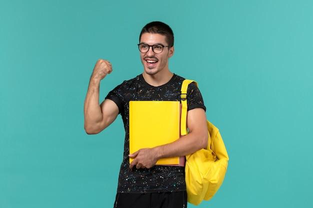 Vista frontal de um estudante do sexo masculino em uma mochila de camiseta amarela escura segurando diferentes arquivos e regozijando-se na parede azul claro