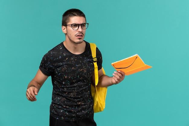 Vista frontal de um estudante do sexo masculino em uma mochila de camiseta amarela escura segurando o caderno na parede azul
