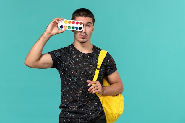 Vista frontal de um estudante do sexo masculino em uma mochila de camiseta amarela escura segurando pinturas na parede azul-clara